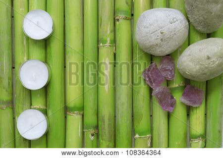 Inspirational scene with three candles aligned, stones and gemstones on a natural green bamboo backg