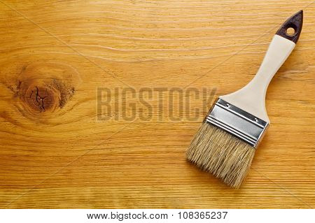 Paint Brush On Varnished Wooden Board With Place For Text