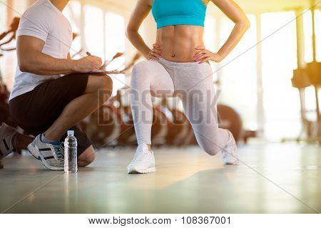 young sporty woman with trainer exercise in fitness gym