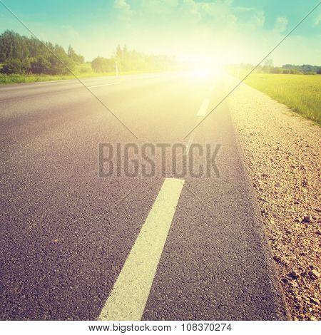 Asphalt country road at sunset. Vintage image.