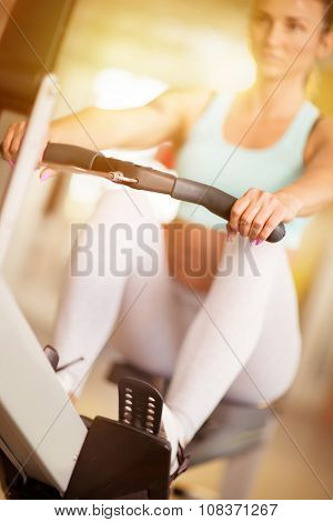 Young girl exercise on row machine at the gym