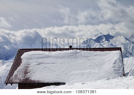 Snowy Roof And Mountains In Clouds