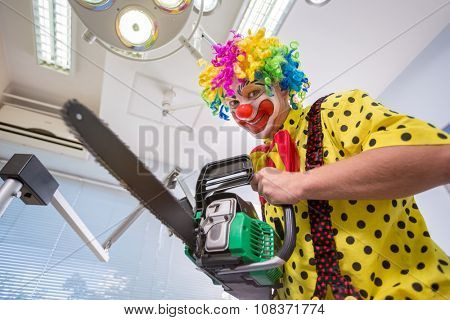Crazy colorful clown make joke with chainsaw in dental clinic