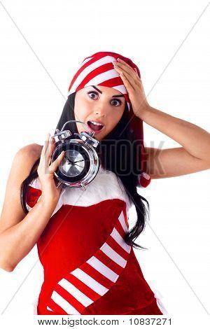 Santa Girl Holding A Clock, Alarm Clock And Wondering. Holidays Christmas And New Year.