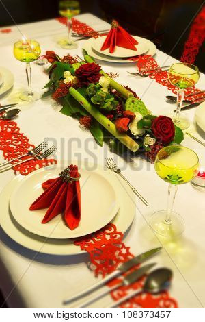 Festive Christmas table decorated with red napkins and flower arrangement