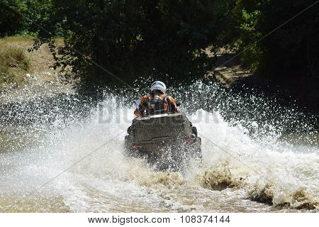 The Man On The Atv Crosses A Stream