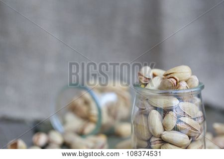 Pistachio nuts in a glass bottle on a wooden surface covered by moss.