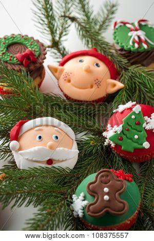 Colorful Christmas cupcake on green branch