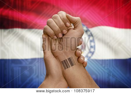 Barcode Id Number On Wrist Of Dark Skinned Person And Usa States Flags On Background - Missouri
