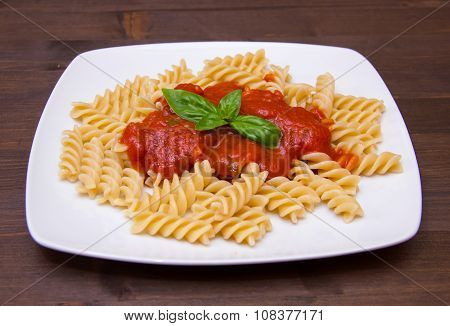 Fusilli with tomato sauce on wood