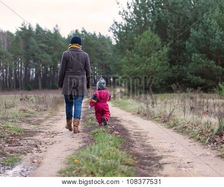 Mother With Child Walking By Rural Sandy Road In Forest