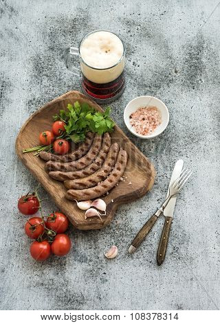 Grilled sausages with vegetables on rustic serving board and mug of light beer over grunge  backdrop