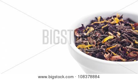 Black dry tea leaves in plate isolated on white