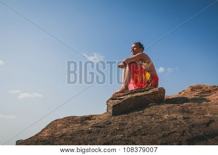 african american black woman sitting and relaxing on a natural coastal rock high up, contemplating the sea against a blue sky