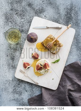 Camembert or brie cheese with fresh figs, honeycomb and glass of white wine on serving board over gr