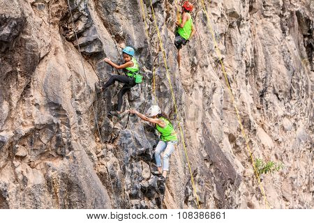 Group Of Teenager Climbers Climbing A Rock Wall