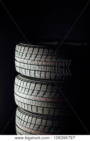 studless winter tires stack, black background