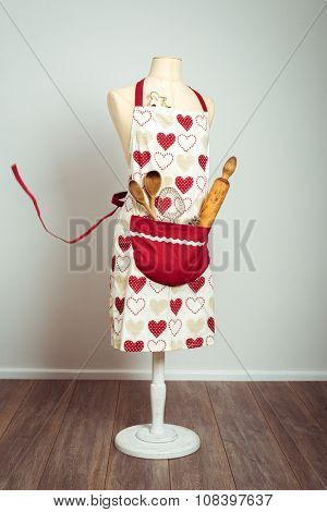 Red apron with pocket filled with utensils