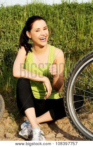 Female tourist with mountine bicycle gesturing ok