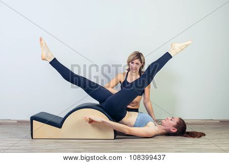Pilates, fitness, sport, training and people concept -  woman with instructor doing  exercises on sm