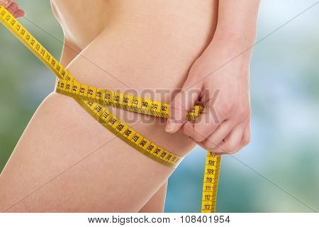 Slim undressed woman measuring her thigh.