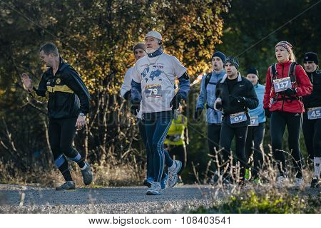 group of athletes running down road in autumn forest