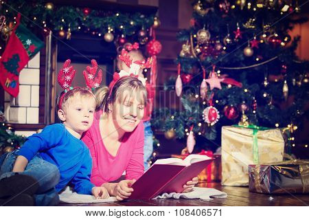 mother and son reading book by fireplace on Christmas