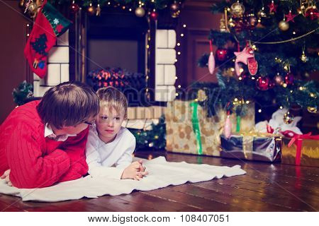 father and son talking by a fireplace on Christmas