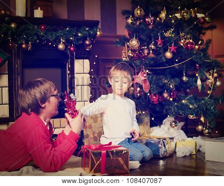 father and son giving presents at Christmas