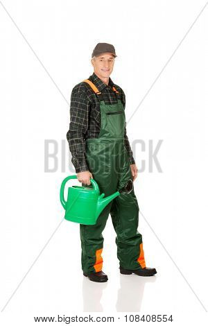 Mature gardener holding green watering can.