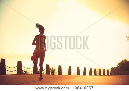 young fitness woman runner running on sunrise seaside