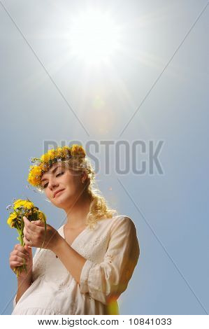 schöne Frau mit Löwenzahn Blumen over blue sky