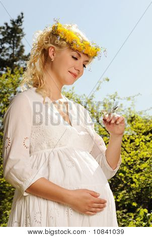Lovely pregnant woman with a butterfly over blue sky