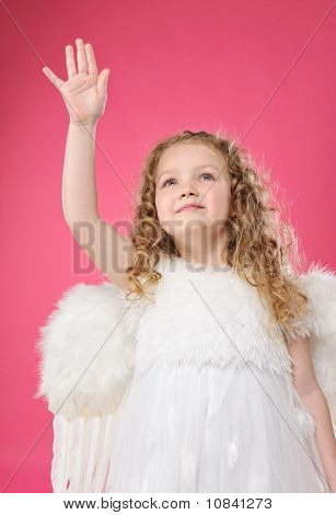 Beautiful little angel girl isolated on pink background