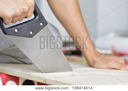 closeup of a young caucasian man sawing a wooden board with a handsaw