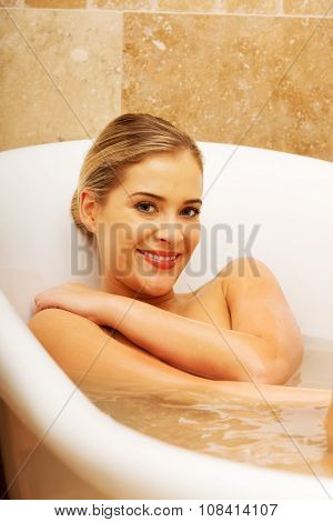 Beautiful woman relaxing in bathtub looking at the camera.