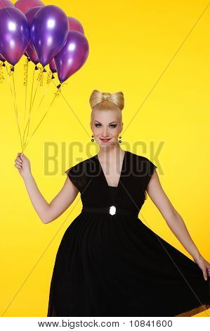 Beautiful lady with a bunch of purple balloons
