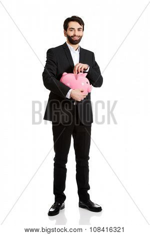 Happy handsome businessman putting a coin to piggybank.