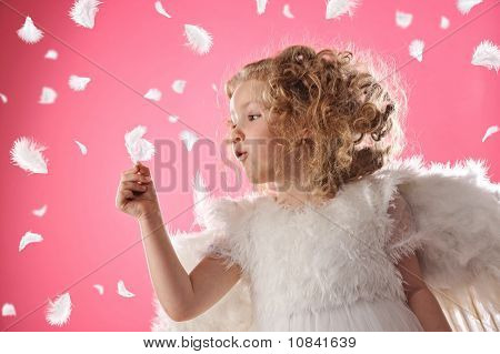 Beautiful  little angel girl holding a feather