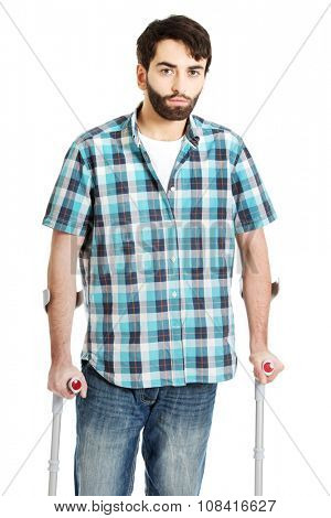Young upset disabled man with crutches.