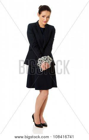 Arrested businesswoman with handcuffs around hands.