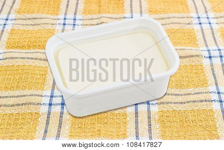 Container Of Feta Cheese On A Checkered Tablecloth