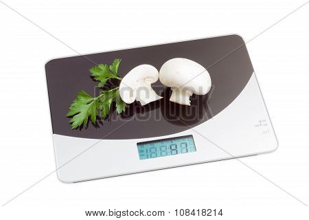 Digital Kitchen Scale With Mushrooms On Light Background