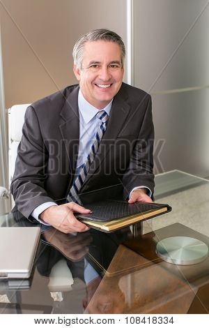 Mature smiling business man with a notebook in an office