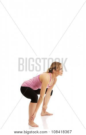 Young active woman doing squats.