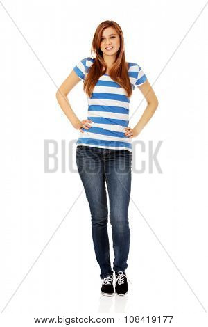 Smiling teenage woman with hands on hips.