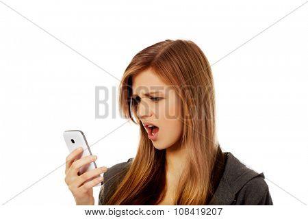 Teenage woman screaming to the phone.