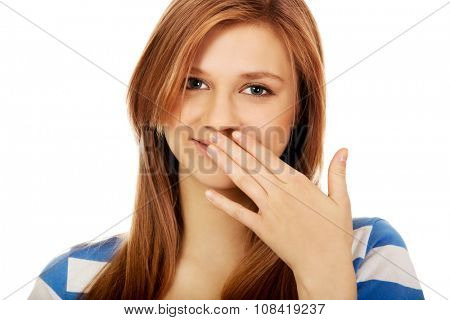 Teenage woman giggles covering her mouth with hand.