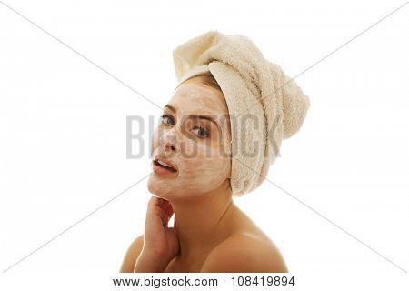 Woman with cream lotion on face and towel on head.