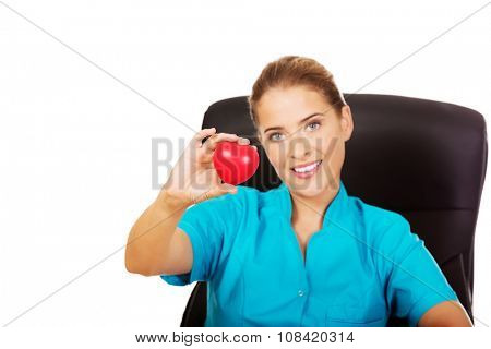 Young female doctor holding toy heart.